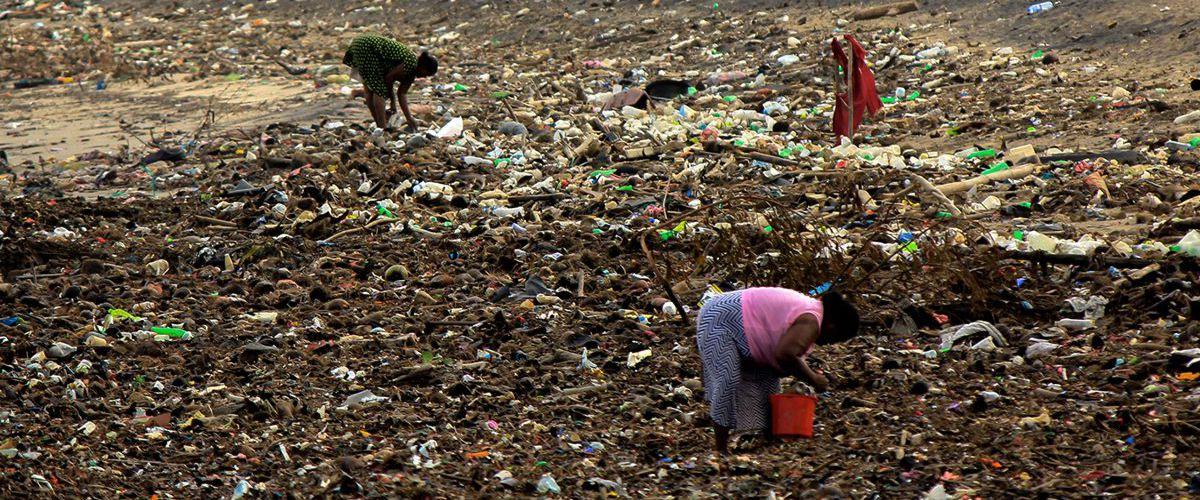 Eine Frau in Armut sucht Brauchbares auf einer stinkenden und rauchenden, riesengroßen Mülldeponie.