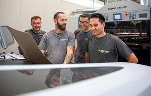 Four technicians talk shop on a new production machine.